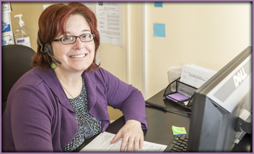 Lady with red hair on headset with purple sweater.